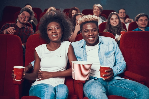 Pareja afroamericana mira comedia en cine.