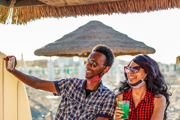 Pareja afroamericana tomando selfie en fiesta en la playa - jóvenes amigos con mascarilla bebiendo cócteles en vacaciones