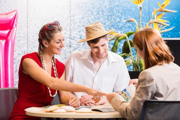 Pareja en agencia de viajes reservando viaje de vacaciones