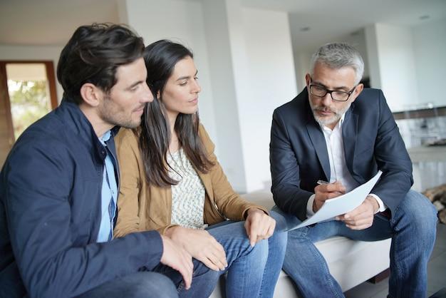 Pareja con agente inmobiliario mirando contrato en casa moderna