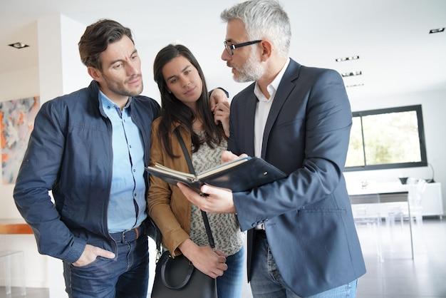 Pareja con agente inmobiliario visitando casa moderna