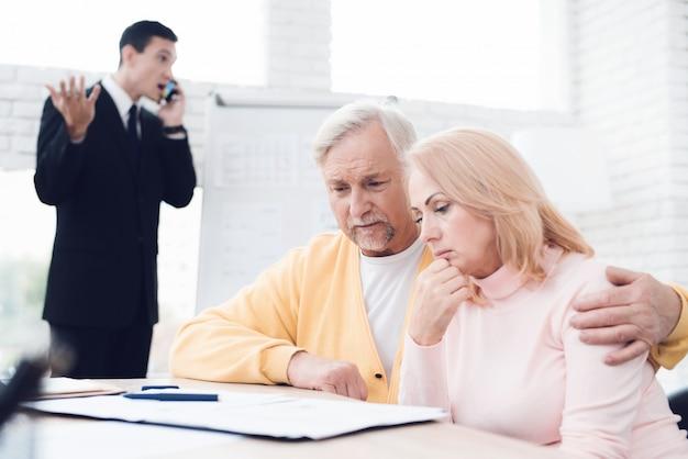 Una pareja agitada de personas mayores en una recepción con un agente de bienes raíces.