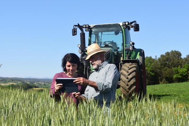 Pareja de agricultores en un campo con una tableta digital