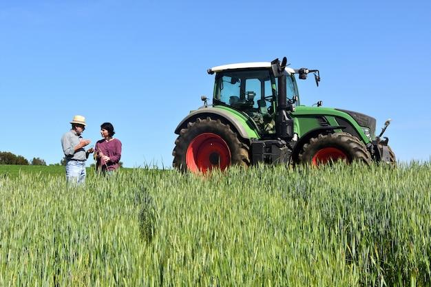Pareja de agricultores en un campo de trigo con un tractor