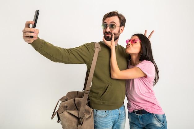 Pareja aislada, mujer muy sonriente en camiseta rosa y hombre en sudadera con bolsa de viaje, jeans y gafas de sol, divirtiéndose, viajando juntos haciendo una foto divertida selfie en el teléfono
