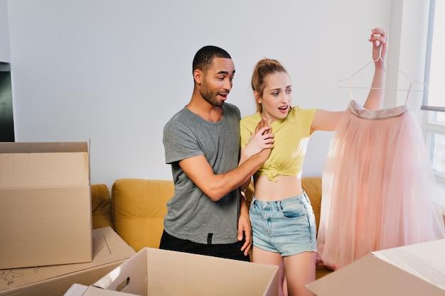 Pareja alegre acaba de mudarse a casa, familia feliz en apartamento nuevo, desembalaje de ropa. chica y chico emocionados por encontrar una hermosa falda rosa. esposa y esposo en una habitación luminosa, con ropa casual.