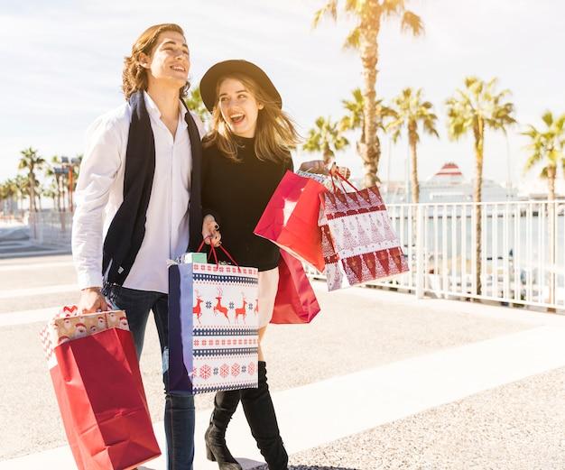 Pareja alegre caminando con bolsas de compras de navidad
