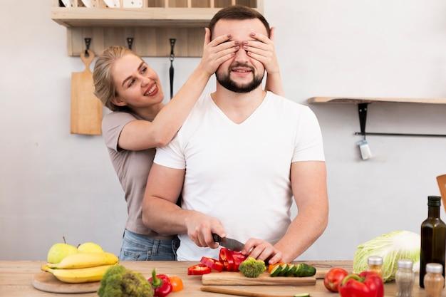 Pareja alegre cocinando en la cocina