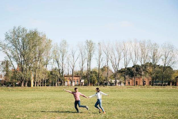 Pareja alegre corriendo por el campo tomados de la mano