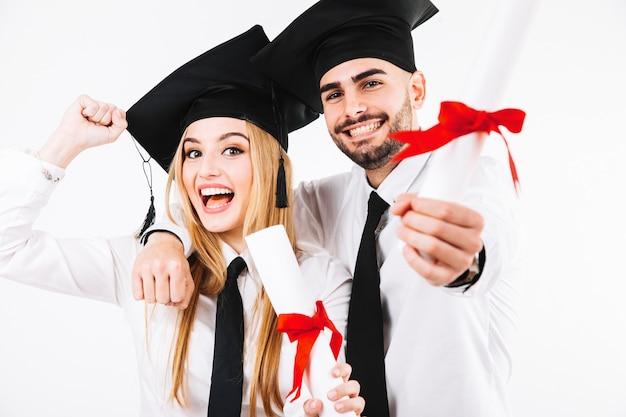 Pareja alegre con diplomas