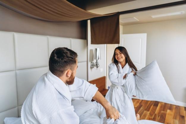 Pareja alegre diviértete en la habitación peleando con grandes almohadas en casa