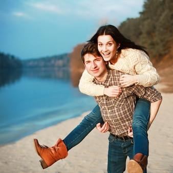 Pareja alegre enamorada divirtiéndose en un lago solitario