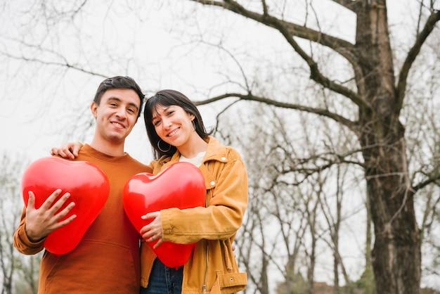 Pareja alegre con globos en forma de corazón