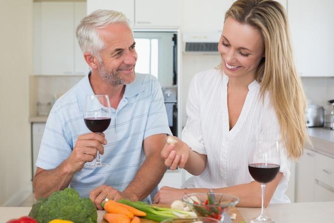 Pareja alegre haciendo la cena juntos y bebiendo vino tinto