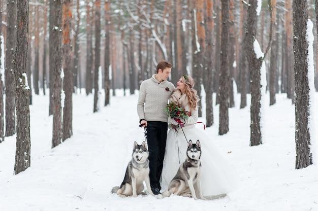 Pareja alegre está jugando con husky siberiano en bosque nevado. boda de invierno