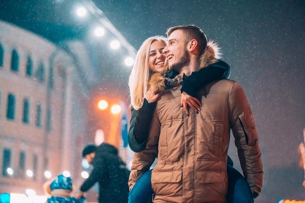 Pareja alegre y juguetona en trajes cálidos de invierno está jugando
