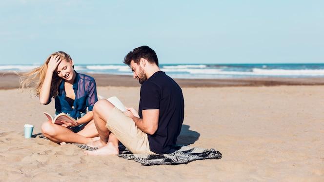 Pareja alegre leyendo libros en la playa