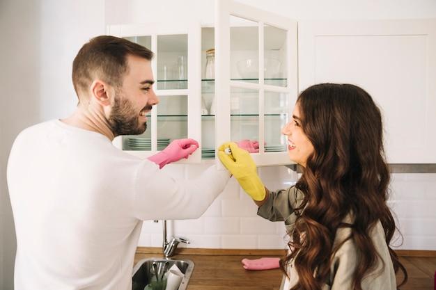 Pareja alegre limpieza cocina juntos