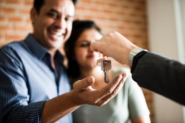 Pareja alegre con las llaves de su nuevo hogar.
