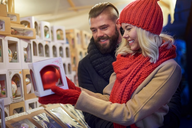 Pareja alegre en el mercado de navidad