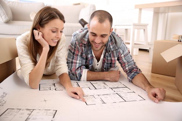 Pareja alegre mirando el plan de construcción de la casa
