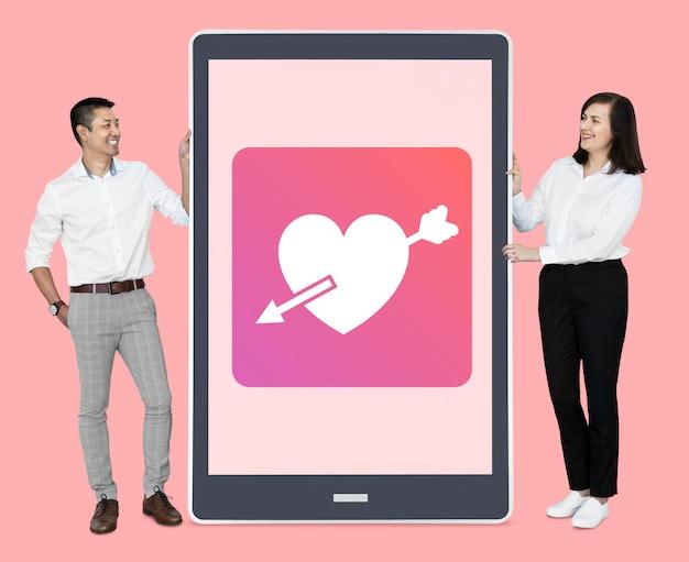 Pareja alegre mostrando citas en línea en una tableta