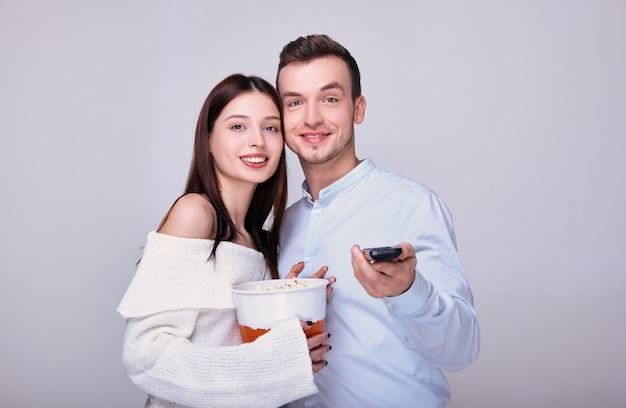 Una pareja alegre con palomitas de maíz sostiene un control remoto de tv.