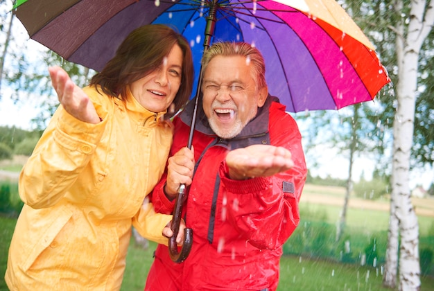 Pareja alegre de pie bajo la lluvia de otoño con paraguas