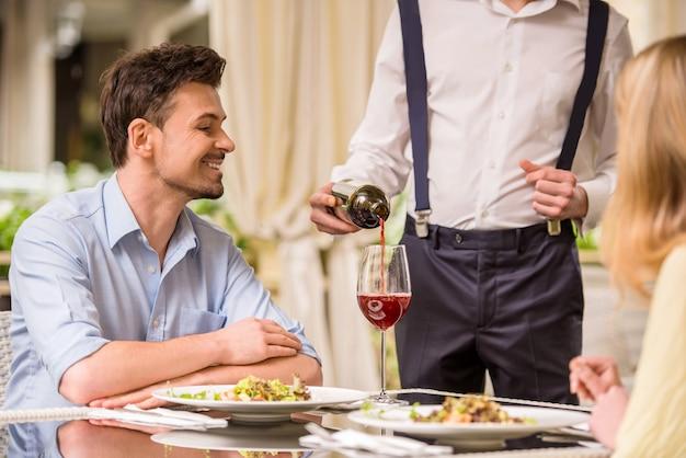 Pareja alegre en un restaurante ordenando vino.