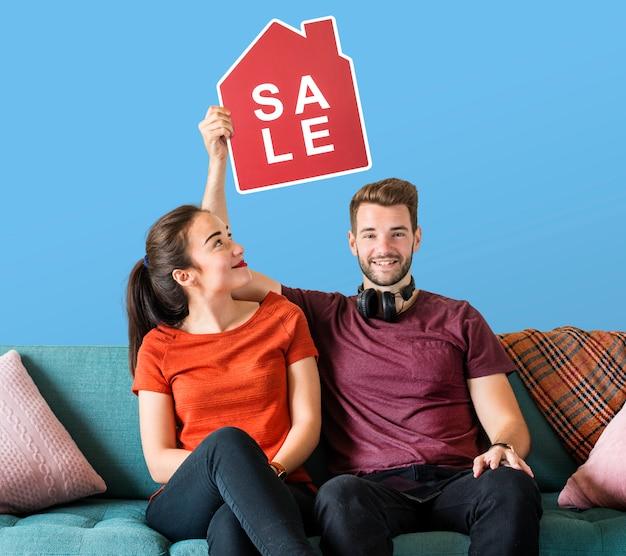 Pareja alegre sosteniendo un icono de venta de casa
