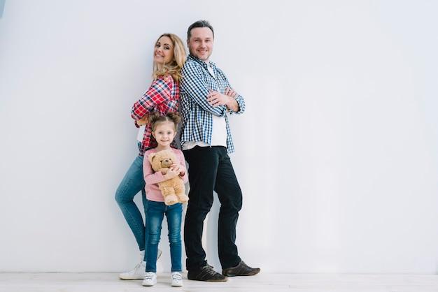 Pareja alegre con su hija posando en frente de pared blanca