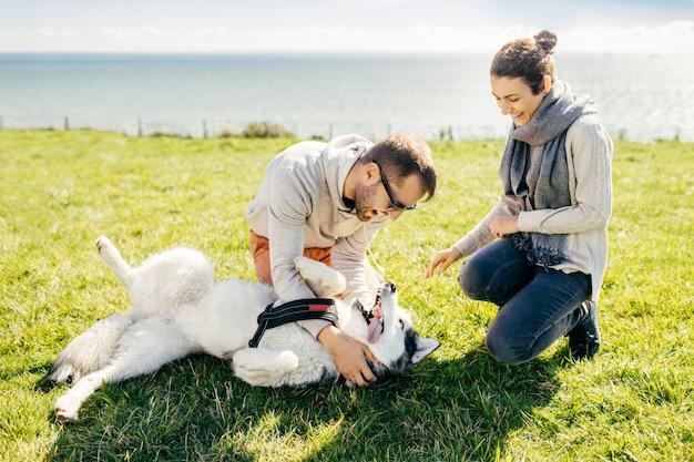 Pareja alegre y su mascota pasan tiempo libre al aire libre