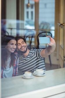 Pareja alegre tomando selfie en café