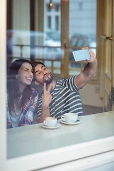 Pareja alegre tomando selfie en cafetería