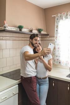 Pareja alegre tomando selfie en cocina