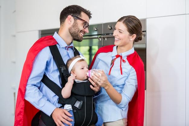 Pareja alegre en traje de superhéroe alimentando leche a hija