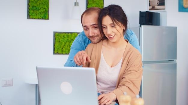 Pareja alegre usando laptop en la cocina leyendo recetas en línea para el desayuno. marido y mujer cocinando comida receta. feliz estilo de vida saludable juntos. familia en busca de comida en línea. sala fresca de salud