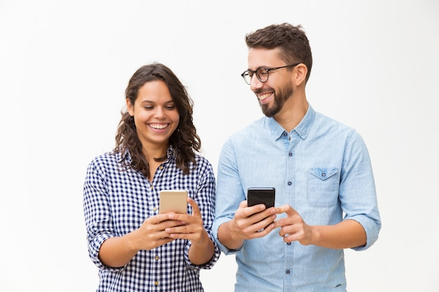 Pareja alegre usando teléfonos inteligentes