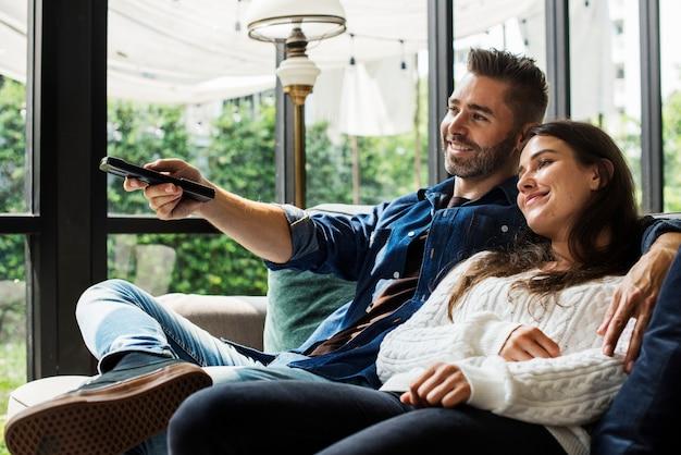 Pareja alegre viendo la televisión juntos