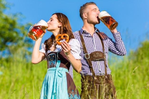 Pareja alemana en tracht con cerveza y pretzel