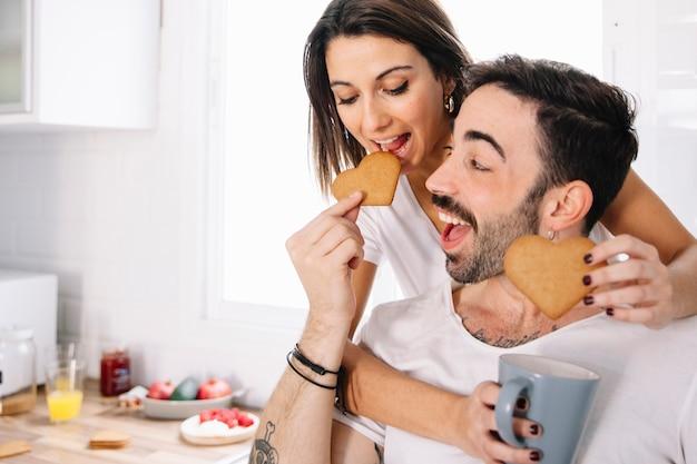 Pareja alimentándose mutuamente con galletas