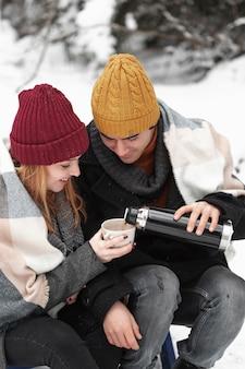 Pareja de alta vista con ropa de invierno que vierte bebidas calientes