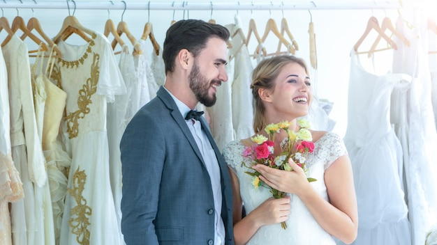 Una pareja ama de pie en el estudio de bodas con un hombre regalar un ramo de flores.