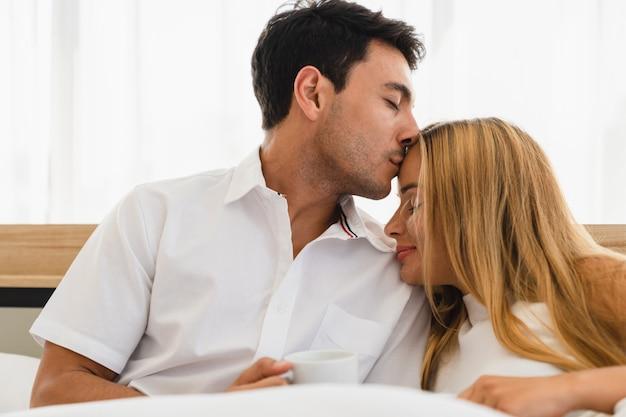 Pareja amante sonriendo y haciendo un beso cálido en la frente de la mujer en el dormitorio