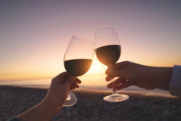 Pareja de amantes bebiendo vino tinto durante la puesta de sol y disfrutando de las vacaciones en el mar en luna de miel