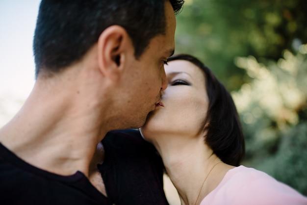 Pareja de amantes besándose, abrazándose y divirtiéndose en las calles de la ciudad - turismo, viajes, personas, ocio y concepto adolescente.