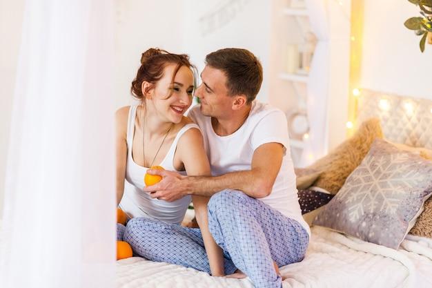 Pareja de amantes en pijama tumbado en el sofá. tiempo de navidad. vacaciones en casa