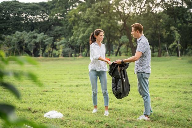 Pareja de amantes voluntarios que usan guantes caminando para recoger la basura en el parque para mantener el medio ambiente limpio