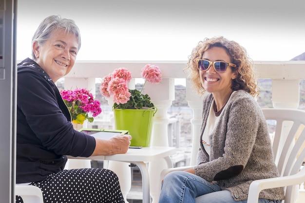 Pareja de amigas se quedan juntas en la terraza disfrutando de la amistad en casa. usando tableta conectada a internet y sonrisa