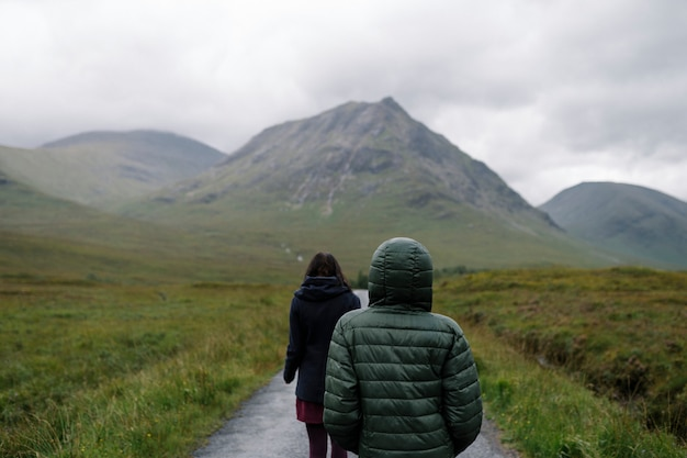 Pareja de amigos caminando a través de la lluvia en glen etive, escocia